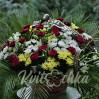 Large funeral basket of roses, chrysanthemums, seasonal flowers