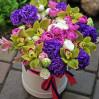 Шляпная коробка с эустомами, розами и орхидеями в ярких тонах